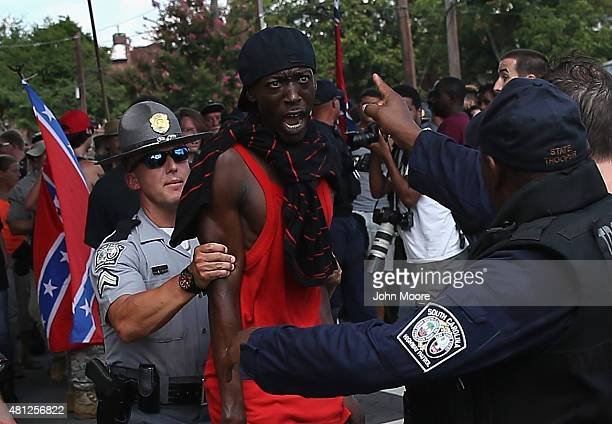 Police restrain a protester as Ku Klux Klan members depart the state capitol building after a Klan demonstration on July 18 2015 in Columbia South...