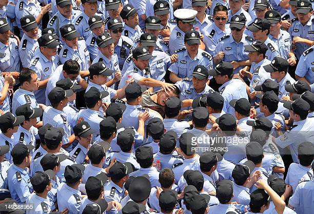 Police restrain a protestor outside the local government offices in the coastal city of Qidong near Shanghai in the eastern China province of Jiangsu...