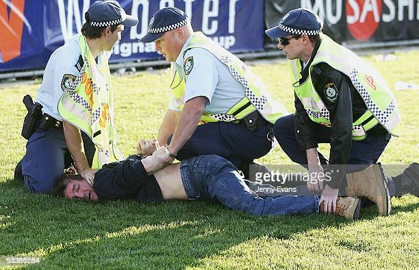 Police restrain a spectator after he ran onto the field after the round 23 NRL match between the Wests Tigers and the North Queensland Cowboys held...