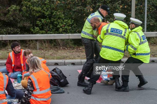 Police restrain an angry motorist as protesters from the Insulate Britain protest group block a major roundabout near the Dartford crossing and M25...
