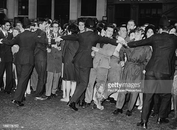 Police restrain crowds of onlookers outside the Old Bailey London as star witness Christine Keeler leaves the trial of Stephen Ward London 25th...