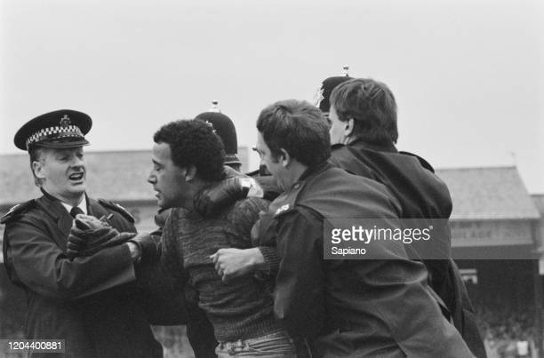 Police restrain football fans during a pitch invasion during the FA Cup Fifth Round replay between Luton Town and Watford at Kenilworth Road, Luton,...
