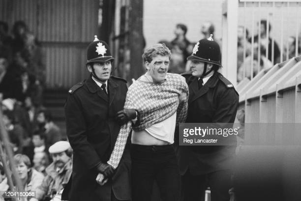 Police restraining a football fan at the FA Cup Fifth Round replay between Luton Town and Watford at Kenilworth Road in Luton, England, 9th March...