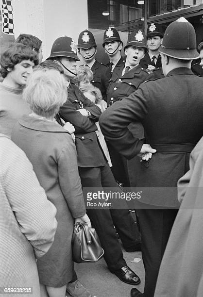 Police restraining the crowd outside the Beatles' Apple boutique on the day of its closing when all its remaining stock was given away London 31st...