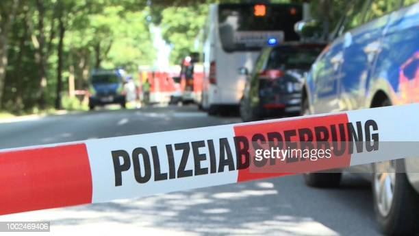 Policemen secure a street where a public service bus stands in which a passenger attacked fellow travellers with a knife in the afternoon of July 20...