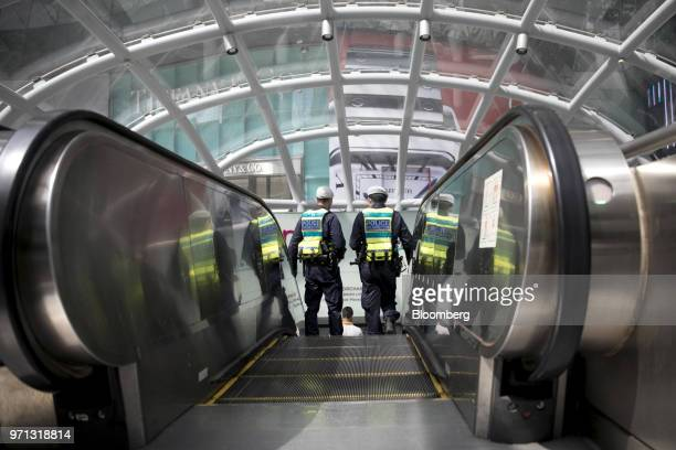 Police ride an escalator at an Mass Rapid Transit train station in Singapore on Monday June 11 2018 PresidentDonald Trumpis about to see whether...