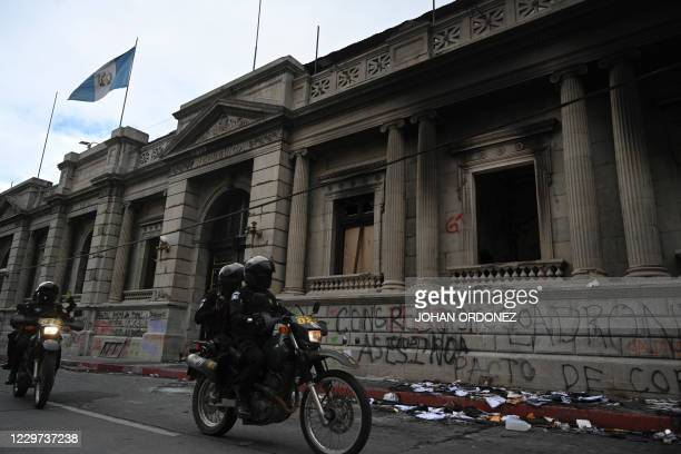Police ride past the Congress a day after it was patrly burned during a protest demanding the resignation of Guatemalan President Alejandro...