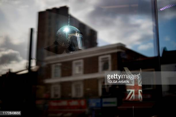 Police riot helmet is repurposed as a disco ball in a shopfront displaying a mini exhibition by secretive British artist, Banksy with the sign 'Gross...