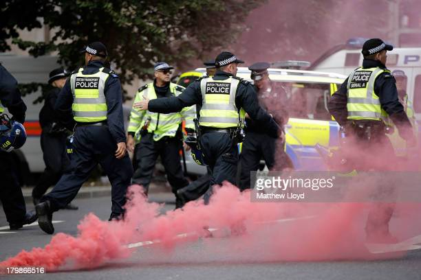 Police run after antifascist protestors who have thrown a smoke bomb at members of the English Defence League during a confrontation at Tower Bridge...