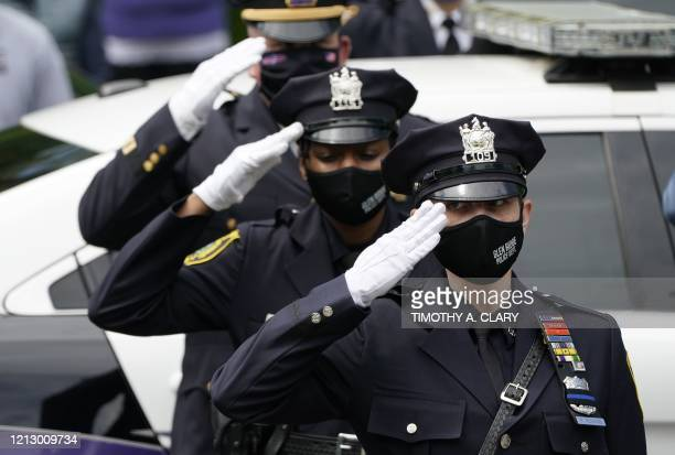 Police salute as the casket of the late Glen Ridge Police Officer Charles Rob Roberts who died of coronavirus weeks after contracting the disease...