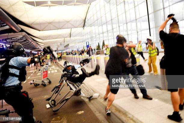 TOPSHOT Police scuffle with prodemocracy protesters at Hong Kong's international airport on August 13 2019 Hundreds of flights were cancelled or...