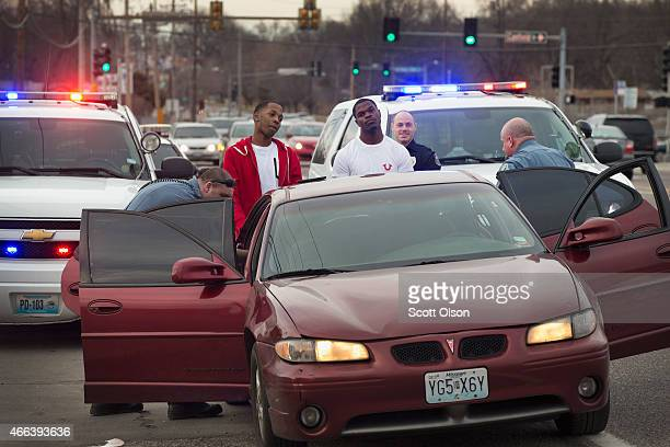 Police search a vehicle while the occupants stand with their hands on the trunk of the car on March 14 2015 in Ferguson Missouri After the car was...