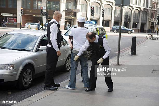 Police search a young black man whose car they had just stopped as he drove through the City of London. Police powers of 'stop and search' are...