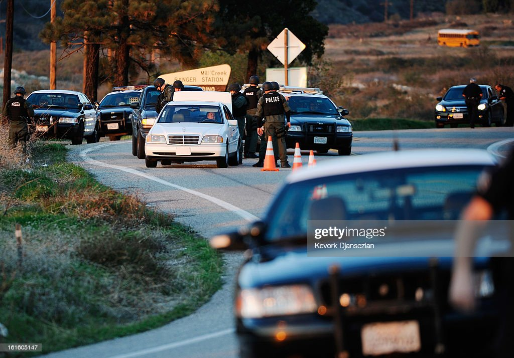 Police search cars at a blockade as they come down off the mountain during a manhunt for the former Los Angeles Police Department officer Christopher Dorner, who is suspected of triple murder, on February 12, 2013 in Yucaipa, California. Dorner barricaded himself in a cabin near Big Bear, California and is in a standoff with authorities after shooting two police officers, killing one and wounding the other. Dorner, a former Los Angeles Police Department officer and Navy Reserve veteran, is wanted in connection with the deaths of an Irvine couple and a Riverside police officer.