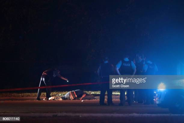 Police search for evidence after a man was found shot to death on the near west side on July 3, 2017 in Chicago, Illinois. Five people were killed...