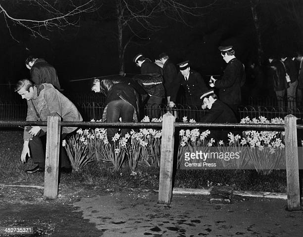 Police search for evidence in flower beds by the Mall, following an attempt, earlier that evening, to kidnap Princess Anne, London, 20th March 1974....