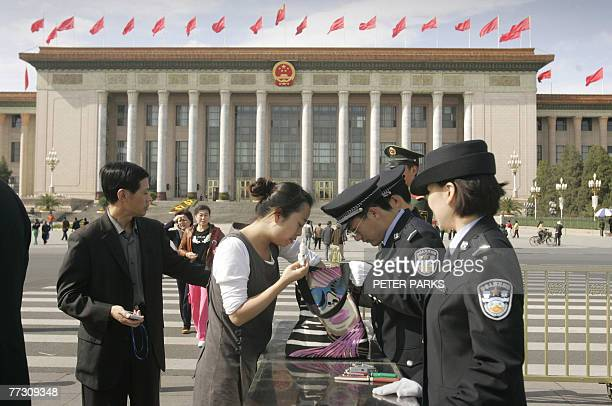 Police search the bags of visitors to Tiananmen Square 12 October 2007 in front of the Great hall of the people where the 17th National Congress of...