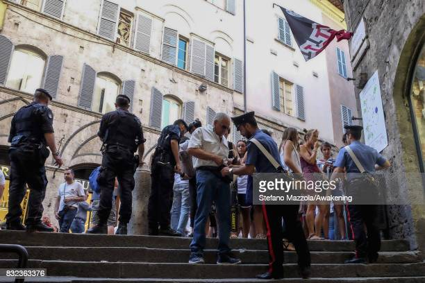 Police search visitors before entering into Piazza del Campo during the dry run ahead of tomorrow's Palio on August 15 2017 in Siena Italy The Palio...