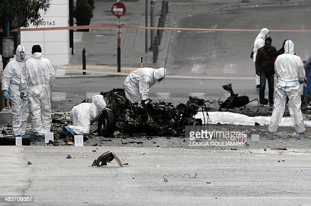 Police searches the wreckage of a boobytrapped car that exploded outside the Bank of Greece on April 10 2014 in Athens The blast did not injure...