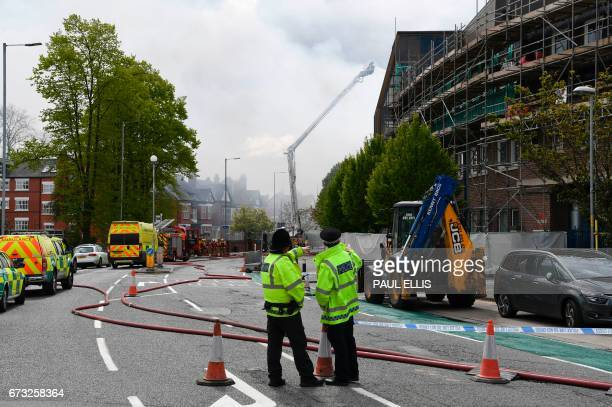 Police secure a cordon as firefighters tackle a blaze on the roof of a building housing offices and laboratories at the front of the Christie...