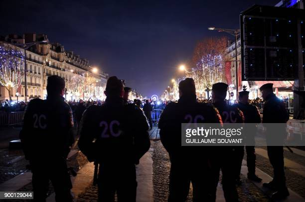 Police secure a street near the Arc De Triomphe as revellers depart New Year celebrations on January 1 2018 in Paris / AFP PHOTO / GUILLAUME SOUVANT