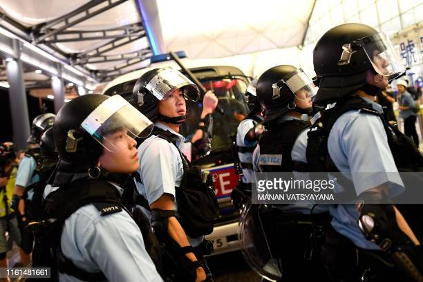 Police secure Terminal 1 after a scuffle with prodemocracy protesters at Hong Kong's international airport on August 13 2019 Hundreds of flights were...
