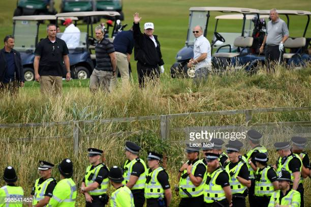 Police secure the area as U.S. President Donald Trump, wearing a hat with Trump and USA displayed on it, waves while playing golf at Trump Turnberry...