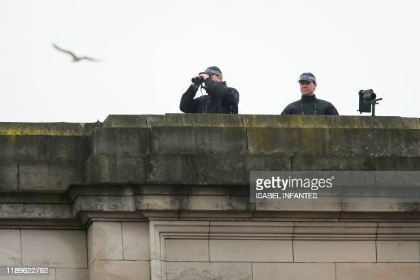 Police secure the area from a roof as they prepare for the Queen to leave Buckingham Palace in London on December 19 2019 headed for the Houses of...
