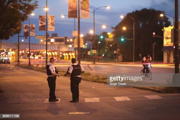 Police secure the crime scene as they search for evidence after three people were shot in the Lawndale neighborhood on July 2 2017 in Chicago...