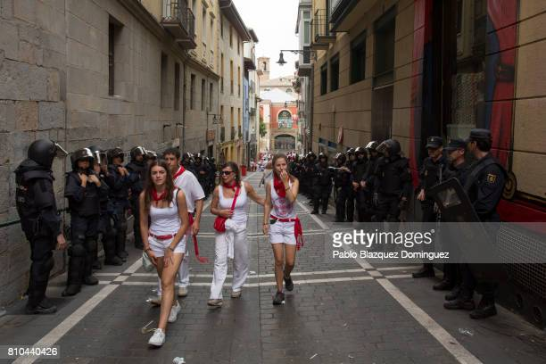 Police secures a street a revellers walk past during the second day of the San Fermin Running of the Bulls festival on July 7 2017 in Pamplona Spain...