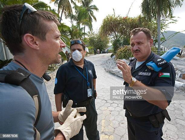 Police security officer for the Jordan Ministry Hisham Kutkut asks a unidentified US citizen a few questions at the destroyed Hotel Montana January...