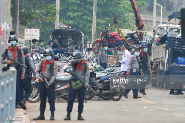 Police seize motorcycles of protesters during a demonstration against the military coup in Naypyidaw on February 18, 2021.