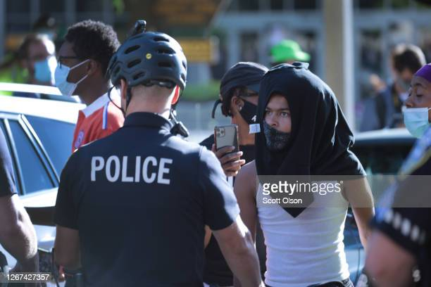 Police separate racial justice demonstrators from counterdemonstrators following a brief clash near the Wisconsin Center as the Democratic National...