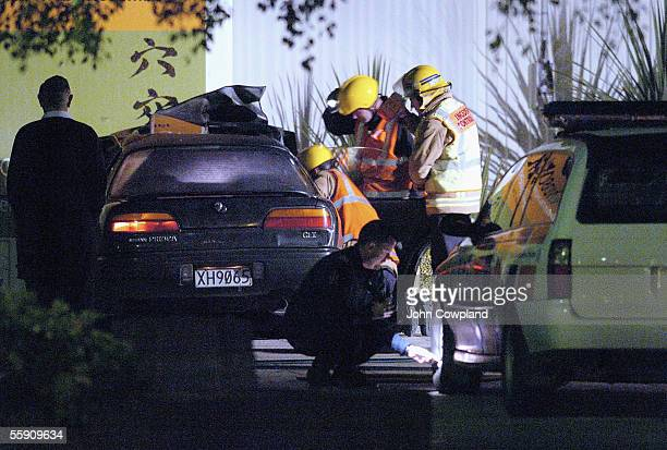 A police serious crash investigator checks a patrol car as fire officers remove the body of the driver from a car that crashed into the wall of the...