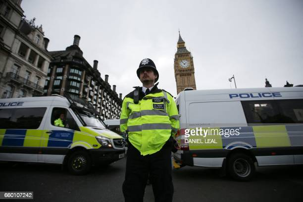 Police set up a cordon to stop traffic from crossing Westminster Bridge in London on March 29 2017 ahead of a vigil by faith leaders and the...