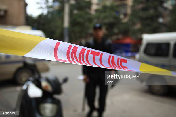 Police set up a line at the crime scene where attackers armed with knives killed three people in Changsha central China's Hunan province on March 14...