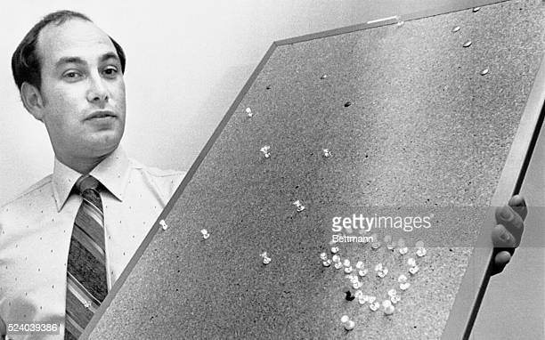 Police Sgt. Wardwell, holds a thumbtack studded bulletin board which police believe to be a part of a map or part of a bizarre game related to his...