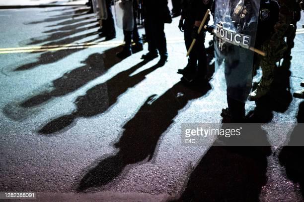 scudi della polizia e ombre contro la protesta degli attivisti - manifestante foto e immagini stock