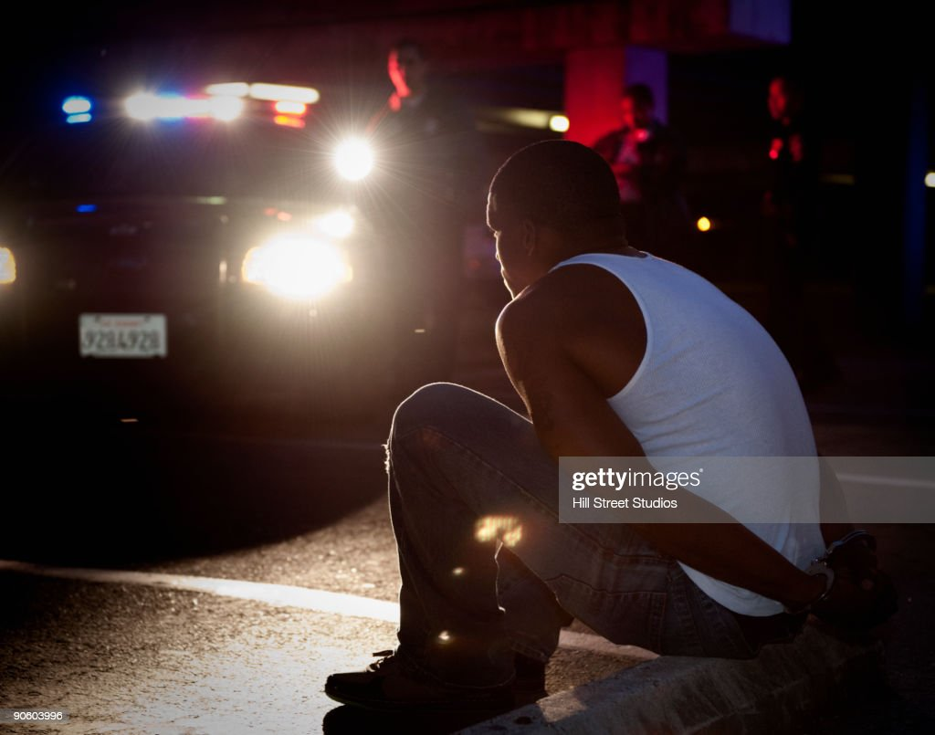 Police shining lights on handcuffed African man sitting on curb : Stock-Foto