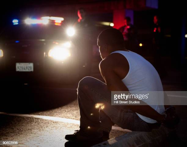 police shining lights on handcuffed african man sitting on curb - handcuffs stock pictures, royalty-free photos & images