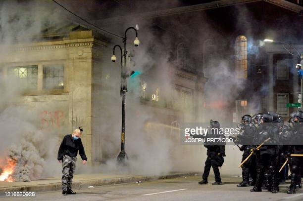 Police shoot pepper spray toward a protester during a demonstration over the death of George Floyd an unarmed black man who died in Minneapolis...