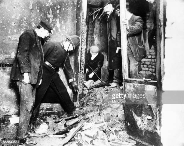 Police sift through the burnt out remains of 100 Sidney Street following a siege and gun battle between members of the Gardstein gang and the police...