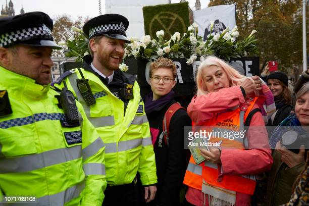 Police smile as they speak to activists marching a coffin symbolising the future of the planet if fossil fuel consumption continues from Parliament...