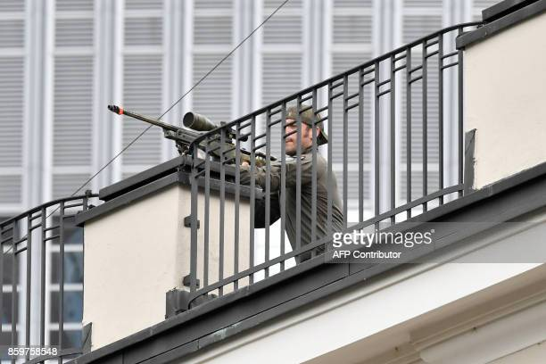 A Police sniper takes up an elevated position prior to the arrival of French President Emmanuel Macron and German Chancellor Angela Merkel before...