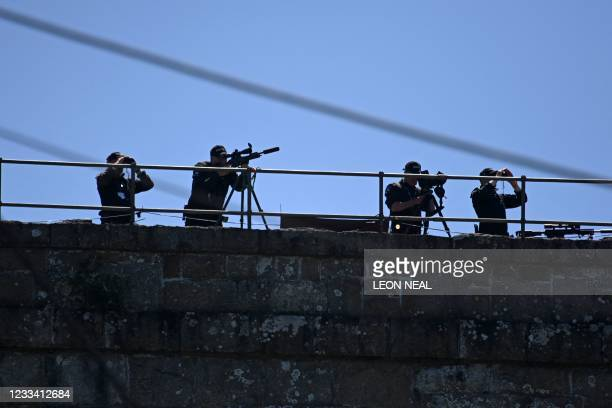 Police sniper team stands in position above the beach as Britain's Prime Minister Boris Johnson and his wife Carrie Johnson arrive to welcome leaders...