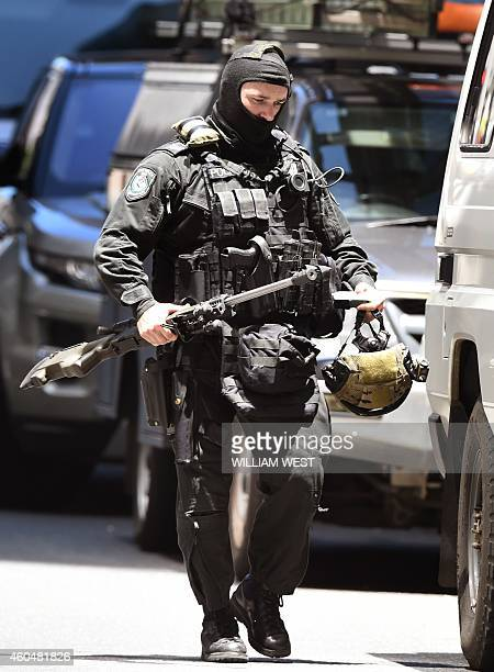 A police sniper walks to his vehicle during a hostage siege in the central business district of Sydney on December 15 2014 Five people ran out of a...