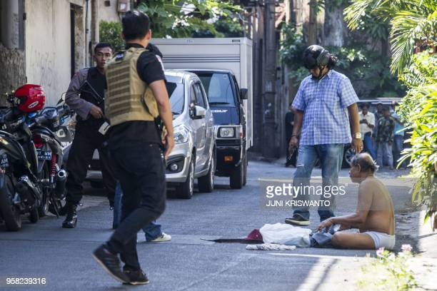 Police speak to a man whom they later took in for questioning as they patrol around the Surabaya police headquarters following a suicide attack in...