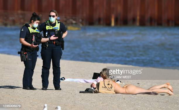 Police speak to a woman enjoying the unusually warm spring weather at St Kilda Beach in Melbourne on September 2 as the city remains in lockdown as...