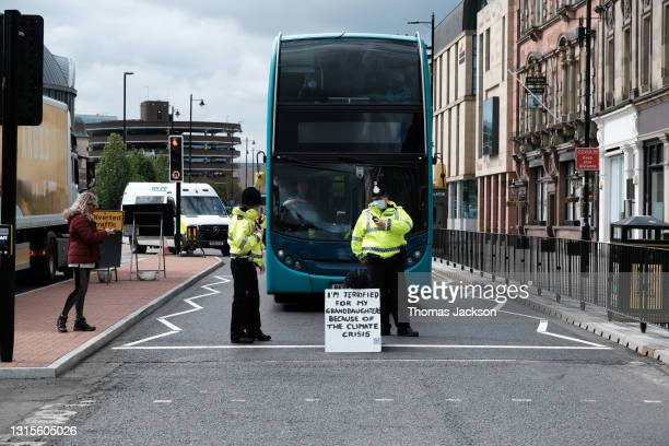 """Police speak to an Extinction Rebellion activist sitting in the middle of the road during a """"Rebellion Of One"""" protest on May 01, 2021 in Newcastle..."""