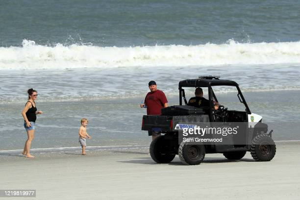 Police speak to people at the beach on April 19 2020 in Jacksonville Beach Florida Jacksonville Mayor Lenny Curry announced Thursday that Duval...
